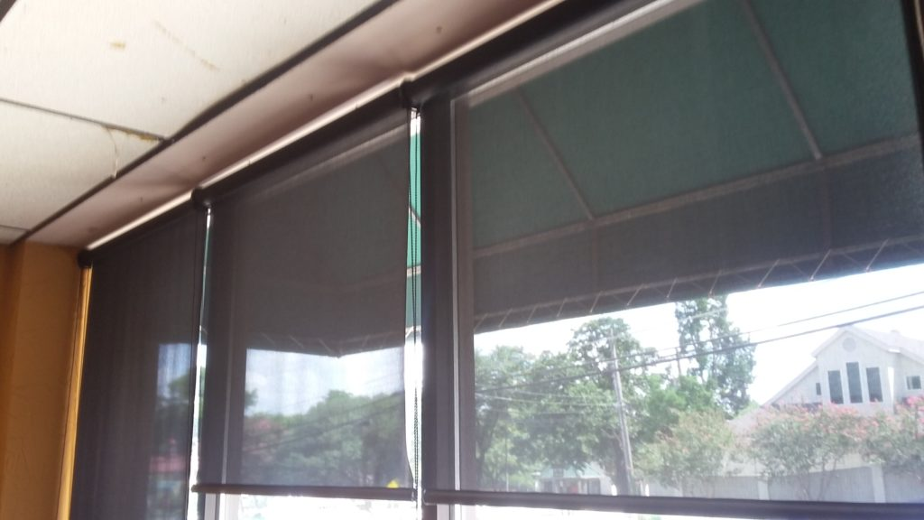 Showing three black 97% Austin TX business window shades installed to provide shade for these windows.