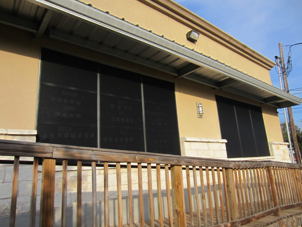 External solar screens mounted on the windows of an Austin Texas commercial building.